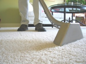 Cleaning white carpet with carpet extraction tool.